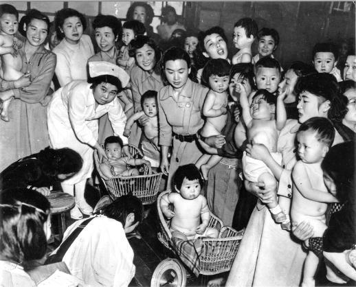 「赤ちゃん審査会」時代の1953年。看護婦さんにかごに乗せられ、きょとん