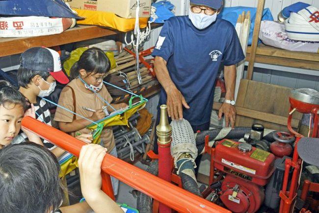 防災倉庫にある消防ポンプをチェックする児童ら(南国市の稲吉公民館)