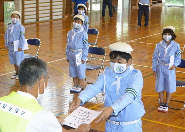 交通少年団の委嘱状を手渡される児童(室戸市の佐喜浜小学校)