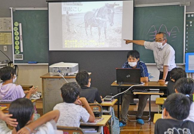 生産者らから稲作の変遷について教わる児童ら(南国市の国府小学校)