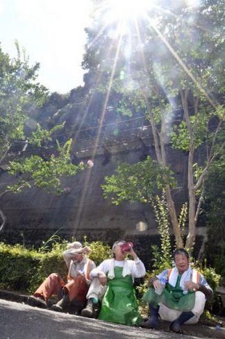 照りつける太陽の下、噴き出す汗を拭う男性ら(21日午後、四万十市西土佐江川崎)