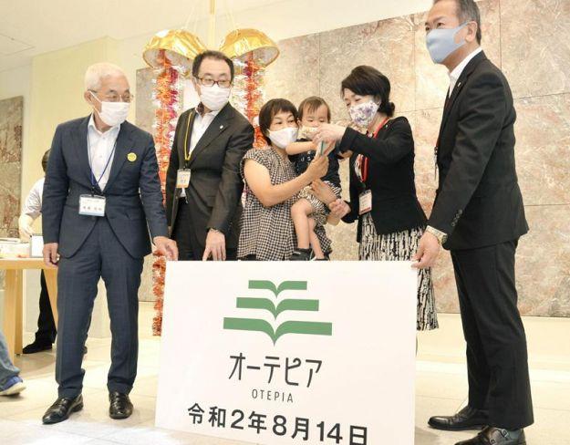 来館200万人の達成を祝う杉本美里さん、健真ちゃん親子=中央=ら(14日午前、高知市のオーテピア)