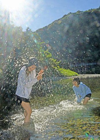 ギラギラと照りつける太陽の下、川遊びを楽しむ親子連れ(14日午後、四万十市伊才原)