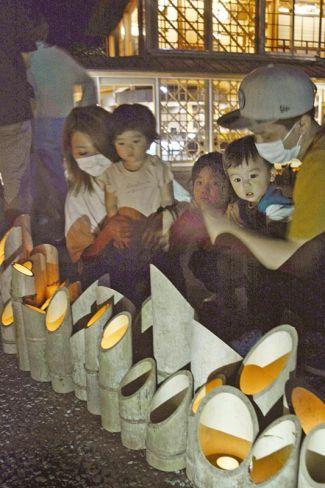 竹灯籠の明かりを楽しむ家族連れら(宿毛市の宿毛まちのえき林邸)