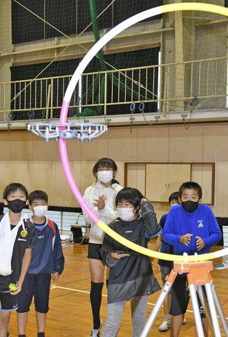 飛行させたドローンの動きを見守る児童ら(南国市の久礼田小学校)