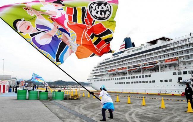 歓迎の大旗が振られる中、入港する「飛鳥Ⅱ」(高知市仁井田の高知新港)