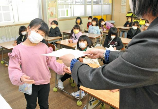 担任から成績表を受け取る小学1年生(高知市の春野西小学校)