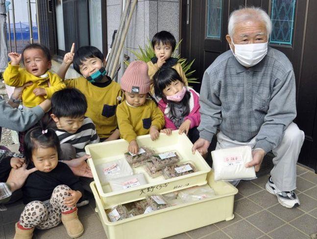 餅と赤飯を配る子どもたち(田野町の大野地区)