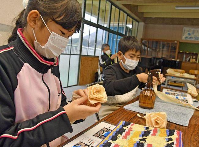 薄く削ったヒノキのかんなくずでバラのコサージュを作る児童ら(四万十市の大川筋中学校)