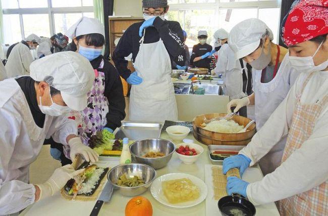 地元女性らに手ほどきを受けながら皿鉢料理を作る6年生(南国市の後免野田小学校)