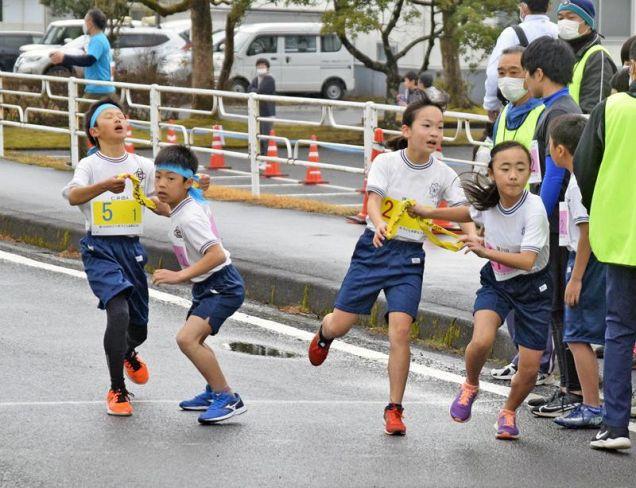 競り合いながらたすきをつなぐ子ども会駅伝のランナー(四万十町本堂)