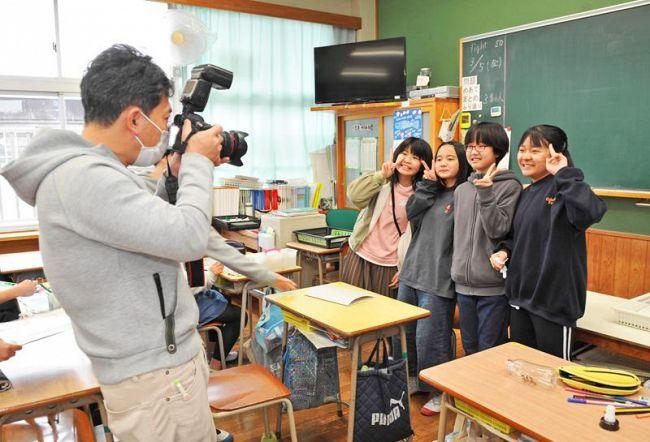 児童にマスクを一瞬外してもらいアルバムの写真を撮影するカメラマン(高知市鴨部の鴨田小)