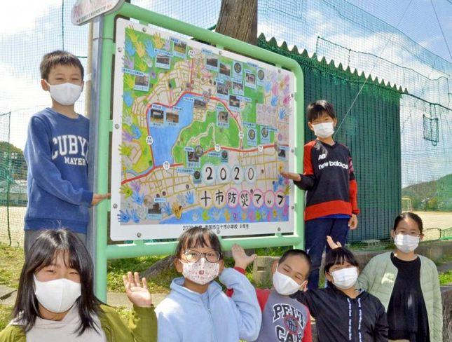 防災マップ看板の前で「地域のみんなで減災意識を高めたい」と話す十市小学校の4年生たち(南国市の同校)