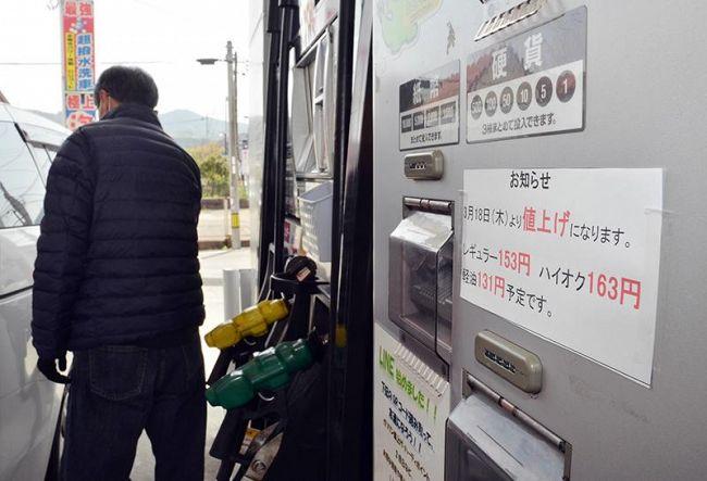 張り紙で18日からの値上げを知らせるガソリンスタンド。急いで給油に訪れた客もいた(高知市東石立町)
