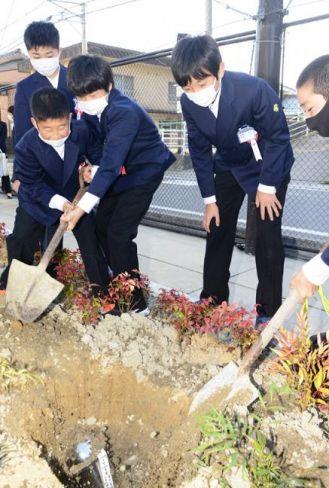 タイムカプセルに土をかぶせる児童ら(宿毛市の宿毛小中学校)