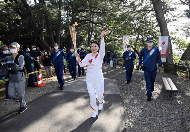 県内での聖火リレーがスタート。トップバッターの島崎和歌子さんが笑顔で進んだ(高知市の桂浜公園)