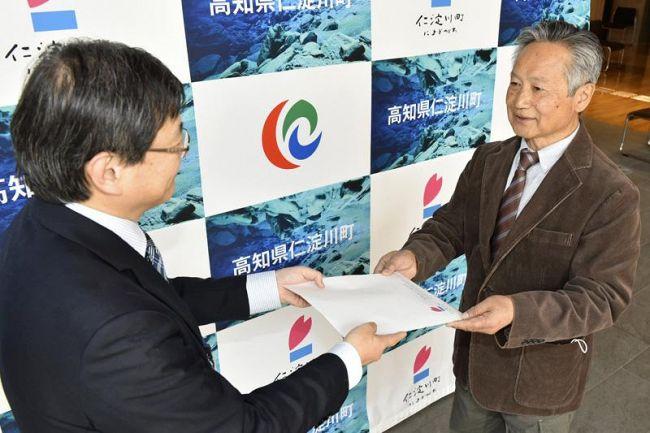 ミツマタの種を受け取るワンアース顧問の大野敏光さん(右)=仁淀川町役場