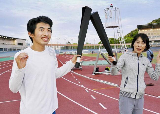 手作りのトーチで本番さながらの練習に励む近藤可連さん=左=と亜矢さん(高知市のりょうまスタジアム)
