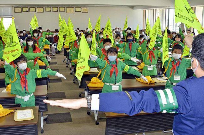 街頭指導で使う旗の振り方を教わる新団員ら(南国署)