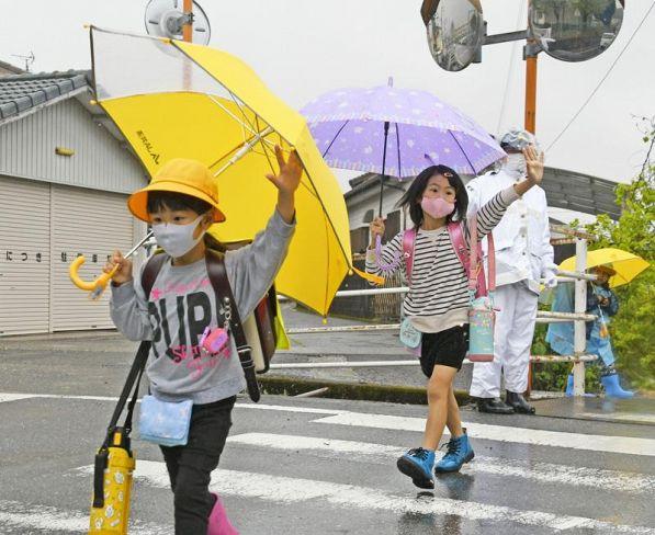 手を上げて横断歩道を渡る蓮池小学校の児童ら(土佐市蓮池)