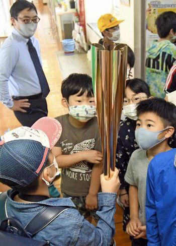 嶋崎賢さん(左奥)が貸し出した実物のトーチを持つ児童=南国市の国府小学校