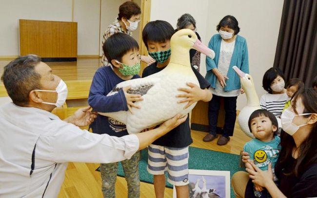 アホウドリの模型を抱いて大きさを体感する児童ら(香南市香我美町下分の山南防災コミュニティセンター)