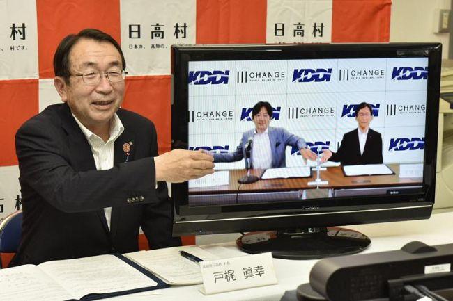 日高村のスマートフォン普及率100%を目指し、KDDIなどと協定を締結した戸梶真幸村長(左)=県庁