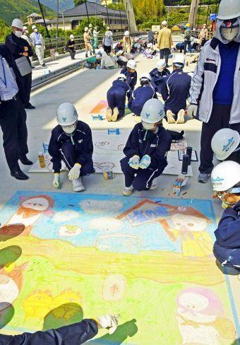 舗装前の橋の上に思い思いにチョークで絵を描く大栃中の生徒ら(香美市物部町大栃)