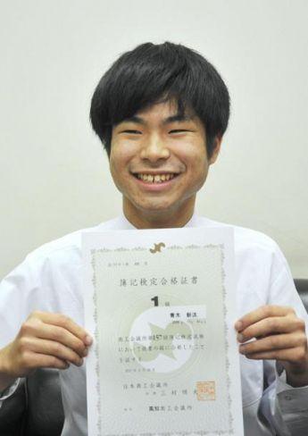 日商簿記検定1級の合格証書を手に笑顔を見せる青木新汰さん(高知新聞社)