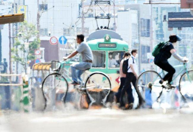 電車も道行く人もゆらり。「逃げ水」現象が見られた(高知市本町5丁目)