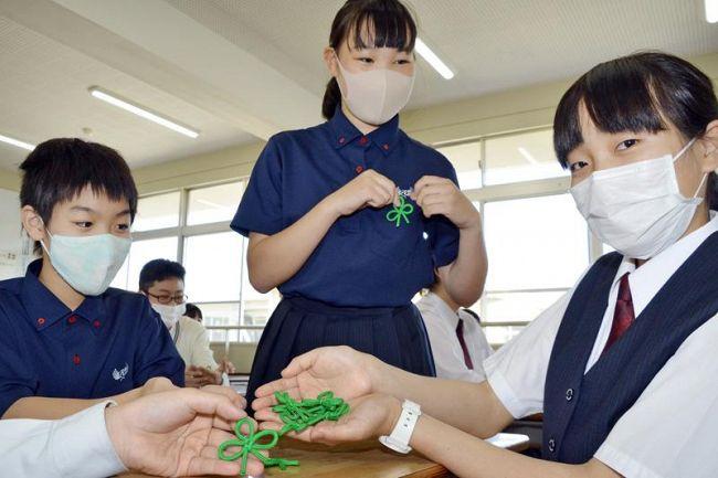 クラスメートにシトラスリボンを手渡す沢田千代子さん(右)と山田咲八乃さん(右から2人目)=高知市の高知国際中学校