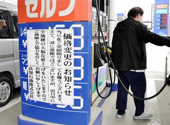 張り紙で14日からの値上げを知らせるガソリンスタンド(11日、高知市南金田)