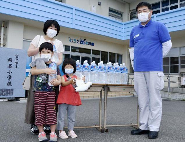 母親や妹と40万人目の記念品を受け取り、喜ぶ宮崎隼人君(左手前)=室戸市室戸岬町のむろと廃校水族館