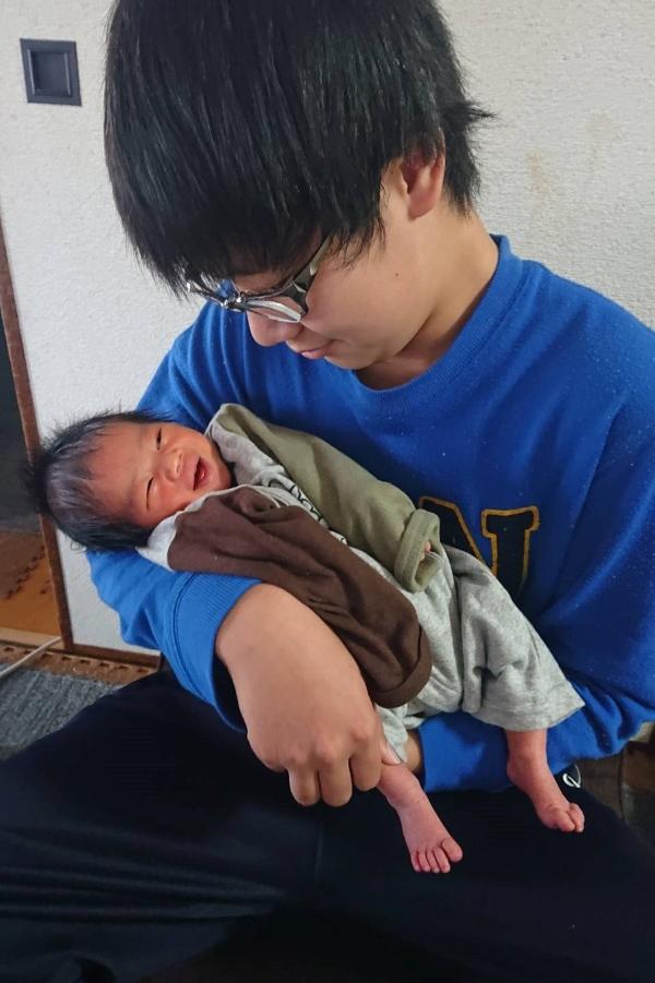 はじめてのお兄ちゃんとの写真。お兄ちゃんに抱っこされて、赤ちゃんもにっこり