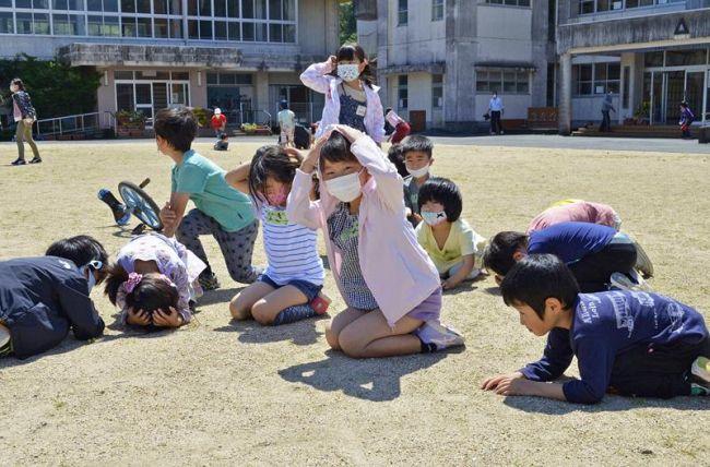 校庭で身をかがめ、頭を守る児童ら(四万十町の東又小学校)