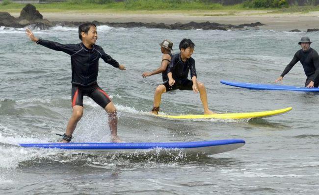 初心者ながら立ち上がって波に乗る児童(黒潮町の浮津海水浴場)