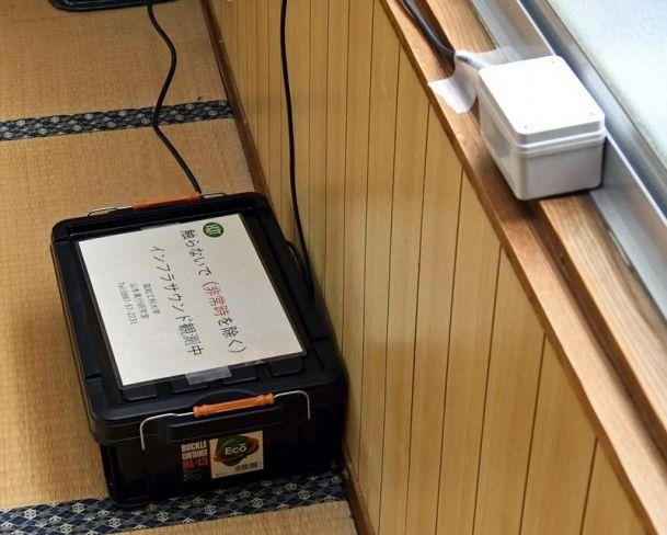 根木屋公会堂の窓際に設置された小型センサー。土砂崩れや地滑りで生じる超低周波音をキャッチする(香美市物部町根木)