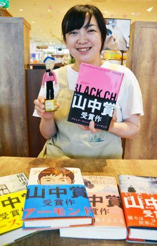 手作りのトロフィー、受賞作を手にする書店員の山中由貴さん(高知市中万々)
