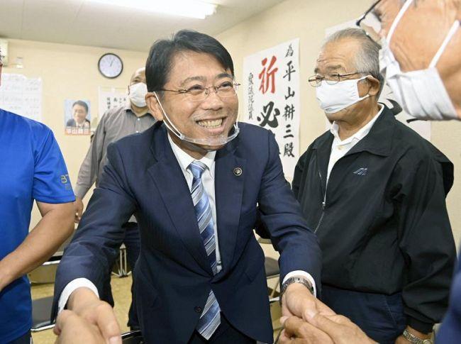 再選を果たし、支持者と握手して喜び合う平山耕三氏(南国市大そね甲)