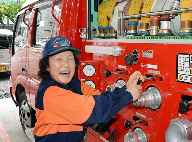 長年操作した消防車の放水設備に触れ、思いを語る田内喜久世さん(高知市内)