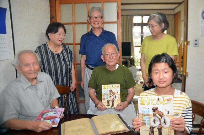 編集長の松本健夫さん=中央=を執筆メンバーで囲む。おいっ子の孫の女の子=手前=らが手にする「百歳記念号」(高知市一宮中町の松本さん宅)