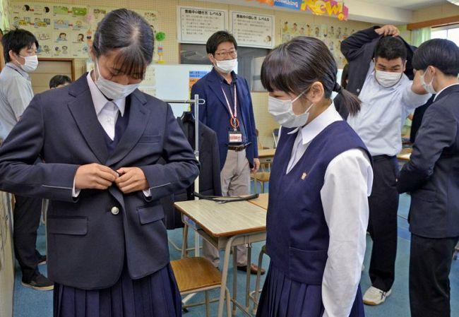 左右どちらの開きにもできるジャケットを試着する生徒たち(南国市立田の香南中学校)