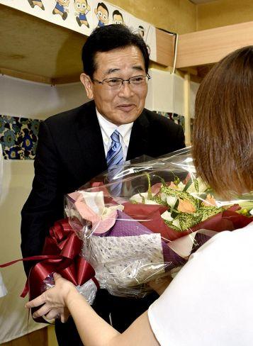 無投票で3選を果たし、花束を受け取る横山幾夫氏(安芸市花園町)