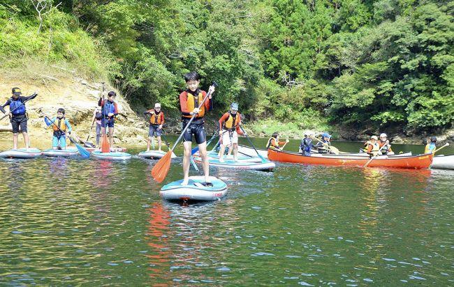 SUPやカナディアンカヌーに乗って湖畔の景色を楽しむ子どもたち(土佐町田井の早明浦ダム湖)