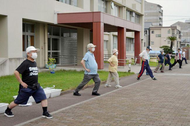 「若い人に世話はかけん」。早朝のラジオ体操で体を動かす高齢者ら(13日、高知市内)