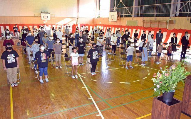 記念式典で校歌を歌う児童や保護者、卒業生ら(土佐清水市の幡陽小学校)