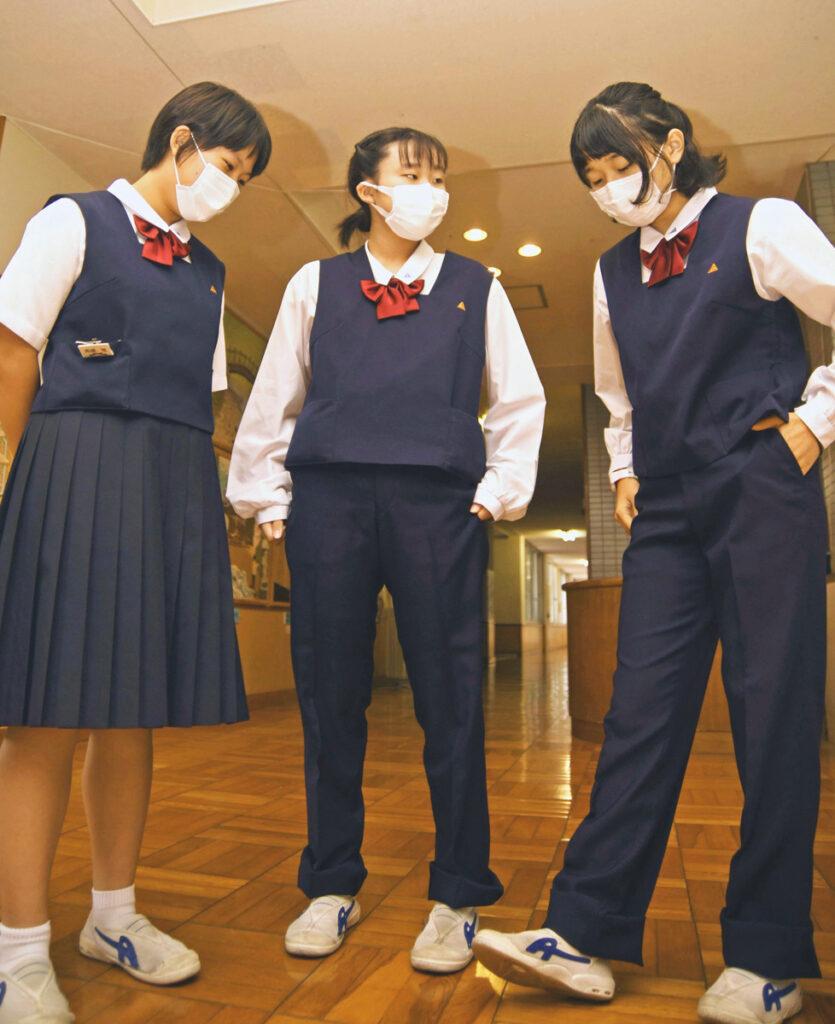 スラックスを試着した香北中生。従来のスカート=左=と比べ「動きやすい」と喜んだ(香美市香北町美良布の同校)