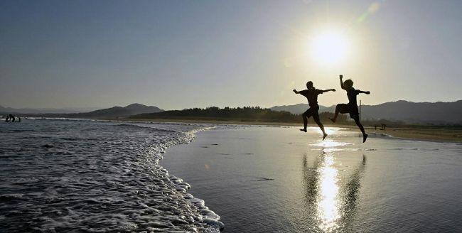 空が映り込んだ砂浜で、海に向かってジャンプ(黒潮町の入野海岸)